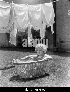 1930S 1940S MÄDCHEN IM FREIEN SITZEN IM WÄSCHEKORB UNTER WÄSCHELEINE VOLLER SHIRTS - Stockfoto