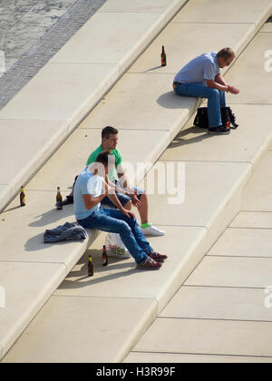 Männer in der Sonne sitzen und trinken Bier am Ufer des Rheins in Köln, Deutschland - Stockfoto