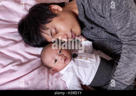Vater schläft vor seinem Babyjungen Säugling liegend auf dem Bett - Stockfoto