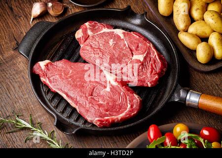 Rohes Rindfleischsteak auf dem Grillpfanne, Kartoffeln, Gewürze und Tomaten auf Holztisch - Stockfoto