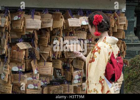 Frau, gekleidet in traditionellen Kimono befasst sich mit Ema Wunsch Plaketten in Ueno Geschichtliches, Tokyo, Japan - Stockfoto