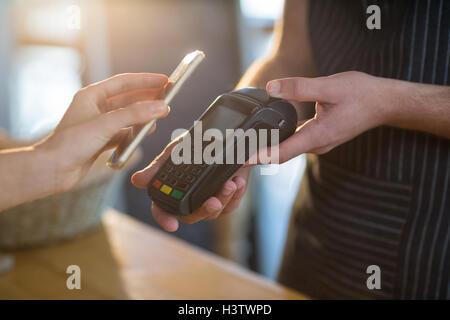 Frau von der Zahlung der Rechnung durch Smartphone mit NFC-Technologie - Stockfoto