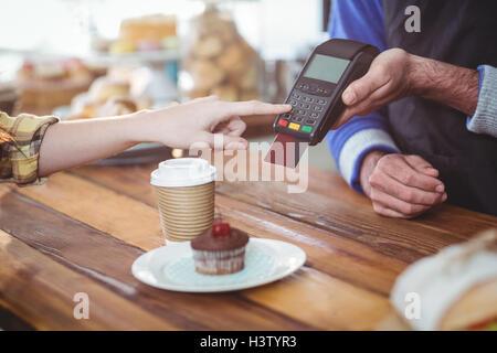 Kunden, die Eingabe der Pin-Nummer in Maschine am Schalter - Stockfoto