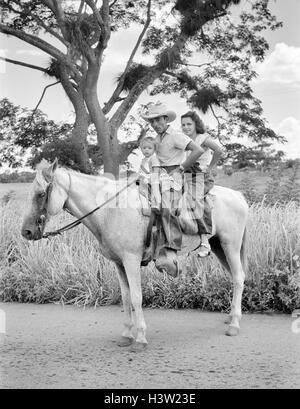 1950ER JAHRE MANN FRAU BABY ALLE SITZEN AUF EINEM PFERD, BLICK IN DIE KAMERA IN DER NÄHE DER STADT SIBANICU IN CAMAGUEY - Stockfoto