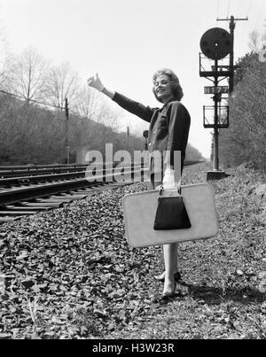 1950S 1960S DAUMEN HALTEN KOFFER STEHEN NEBEN RAILROAD TRACKS BEHANDSCHUHTE HAND LÄCHELNDE FRAU IN DIE LUFT, UM - Stockfoto