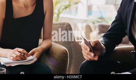 Bild der Geschäftsmann hält Handy und Frau mit Notepad beschnitten. Geschäftsleute sitzen in der Lobby. - Stockfoto