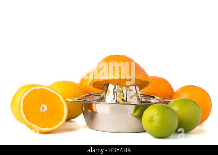 Halben Orange auf Edelstahl orange oder Zitrone hand Saftpresse umgeben von ganzen Zitronen, Orangen und Limetten - Stockfoto