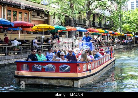 Touristenboot auf San Antonio River entlang dem Riverwalk, San Antonio, Texas USA - Stockfoto