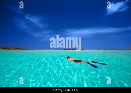 Junger Mann Schnorcheln in tropischen Lagune mit über Wasserbungalows - Stockfoto