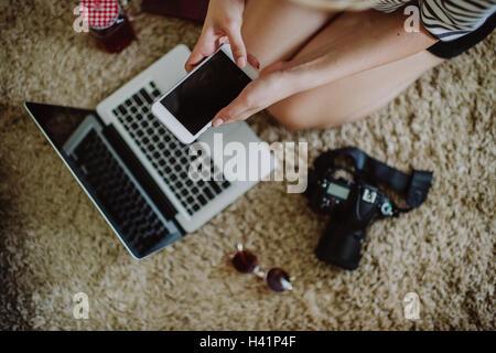 Mädchen kniend am Boden mit Handy - Stockfoto