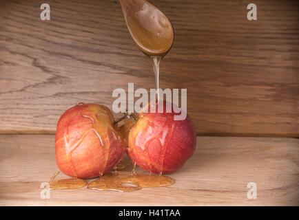 Löffel Honig auf zwei Äpfel gießen - Stockfoto