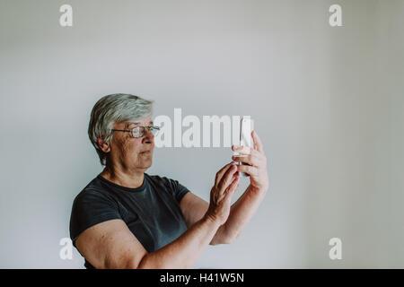 Ältere Frau, die eine Selfie mit einem Mobiltelefon - Stockfoto