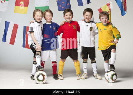 Boys, fünf, Fußballtrikots, Arm in Arm, Gruppenbild, internationale Flaggen - Stockfoto