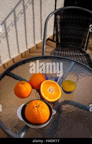 Orange Entsafter, Gläser und Schnitt orange auf einem Glastisch außerhalb ohne Menschen - Stockfoto