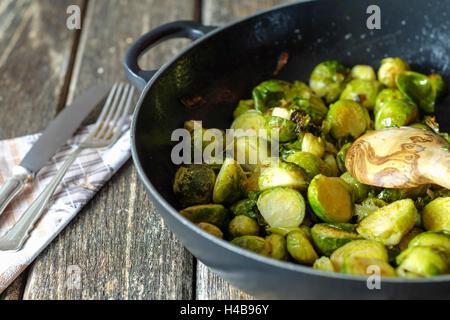Gebratener Rosenkohl in gusseisernen Pfanne auf Holztisch - Stockfoto