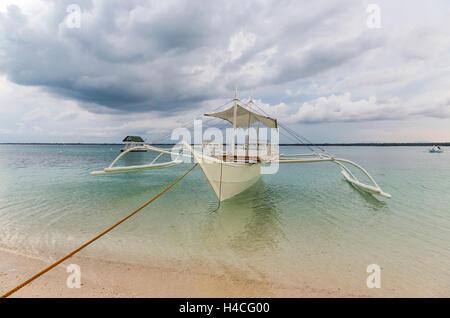 Ein Boot zum Strand von Bantayan Island gebunden - Stockfoto