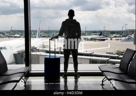 Ein Teenager wartet auf einem Flughafen für den Abflug Stockfoto