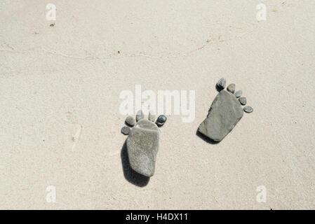 Fußabdrücke von flachen Steinen am Strand gemacht, - Stockfoto