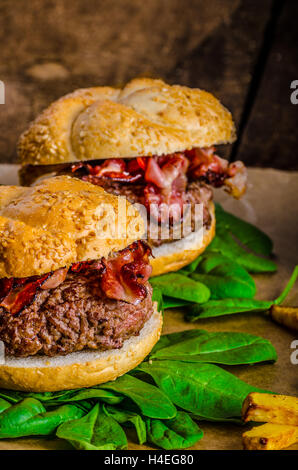 Bacon Burger mit Chili Pommes Frites und Kräuter-Bananen-Smoothie auf Holztisch - Stockfoto