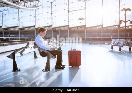 Junger Erwachsener mit Laptop in Flughafen-lounge - Stockfoto