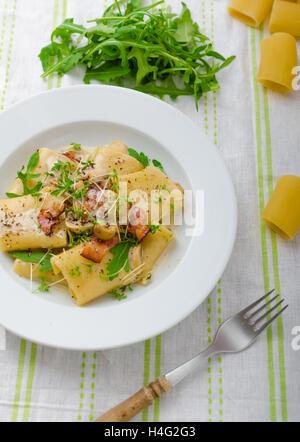 Italienische Rigatoni mit Parmesan-Käse, Parmaschinken und Champignons, Rucola und Microgreens bestreut - Stockfoto