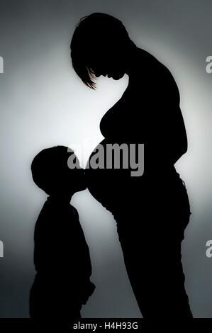 Schwangere Mutter mit Sohn als silhouette - Stockfoto