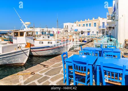 Traditionelle Fischerboote und Taverna Tabellen in Naoussa Hafen, Insel Paros, Griechenland - Stockfoto