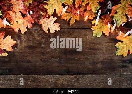 Rustikale Herbst Herbstlaub und dekorative Leuchten über einen rustikalen Hintergrund der Scheune Holz im Hintergrund. - Stockfoto