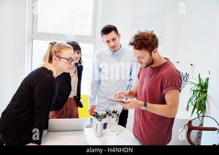 Vier Personen um einen Tisch bei einem Geschäftstreffen, einem digitalen Tablet-Bildschirm betrachten. - Stockfoto