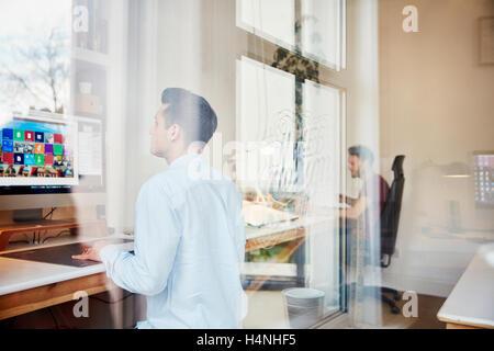 Zwei Männer, die Arbeit am Computer in ein Design-Studio, Blick durch ein Fenster und Reflexionen der Fensterrahmen und Bäume.