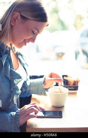 Junge Frau Kaffee trinken und im Chat auf Handy - Stockfoto