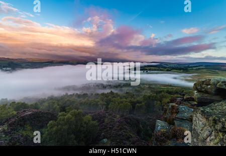 Bunte Sonnenaufgang Wolken über Tal im Nebel mit Fotografie Kamera am Rande der Felsen bedeckt - Stockfoto