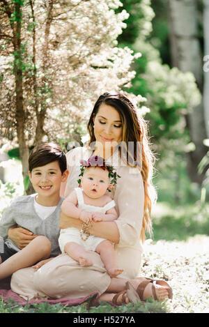 Porträt von ein lächelndes Baby, Mutter und junge Mädchen mit einem Blumen-Kranz auf dem Kopf, sitzt in einem Garten. - Stockfoto