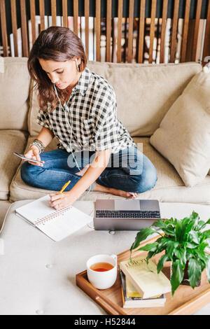 Frau mit langen braunen Haaren sitzen auf einem Sofa mit einem Laptop-Computer und Notebook, arbeiten. - Stockfoto