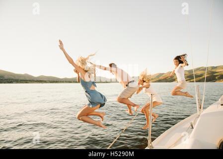 Vier Menschen an der Seite eines Segelbootes in einen See springen. - Stockfoto