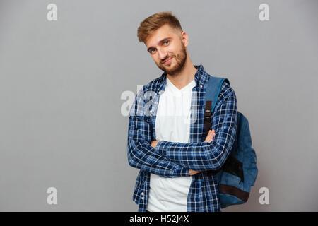 Lächelnd lässigen bärtigen Mann mit Rucksack Stand mit verschränkten Armen auf einem grauen Hintergrund isoliert - Stockfoto