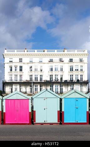 Bunte Strandhäuschen vor viktorianischen Gebäuden, Brighton Beach, Brighton, East Sussex England UK - Stockfoto