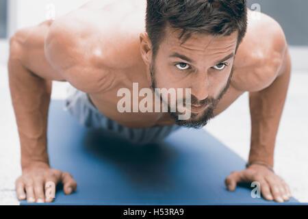 Kraft und Motivation. Schönen jungen Mann tun Liegestütze in Turnhalle - Stockfoto