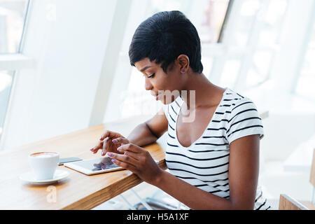 Attraktive afrikanische Geschäftsfrau mit Tablet Amd mit Kaffeepause im Büro - Stockfoto