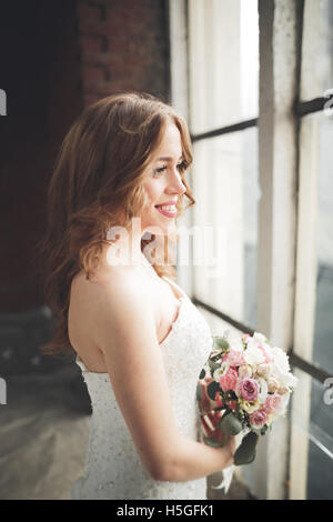 Elegante schöne Hochzeit Braut posiert in der Nähe von großen Fensterbogen Stockfoto