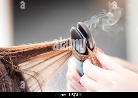 Aufbringen einer geraden Eisens auf eine Frau Frisur Friseur - Stockfoto