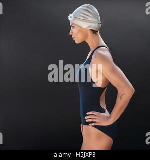 Seite Porträt überzeugt junge weibliche Schwimmer auf schwarzem Hintergrund. Junge Frau im Badeanzug stehen mit - Stockfoto