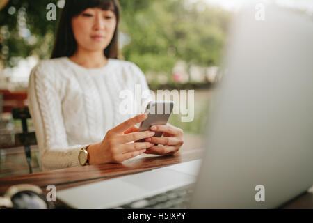 Schuss von Asiatin mit Handy in Straßencafé. Junge Frau mit Laptop lesen SMS-Nachricht auf ihr ce am Tisch sitzen - Stockfoto