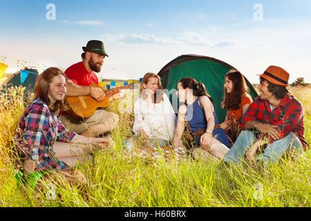 Junge Menschen singen zur Gitarre am Campingplatz - Stockfoto