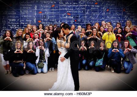 Brautpaar posiert vor der Mur des Je t'Aimes während einer Schulgruppe dahinter machen ein Herzschild, Hand in Hand - Stockfoto