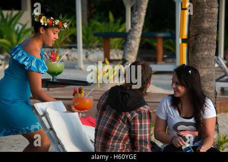 Rarotonga-Insel. Cook Island. Polynesien. Süd-Pazifik. Ein Touristen-paar riesige Cocktails am Strand im Hotel genießen - Stockfoto