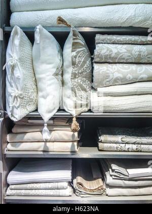 Hellen Kissen, Bettwäsche, Bettdecken und Bett tragen in Regalen - Stockfoto