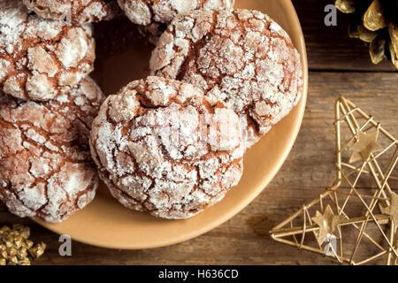 Schokolade crinkle Cookies für Weihnachten mit goldenen Ormaments - hausgemachte festliche Weihnachtsbäckerei - Stockfoto
