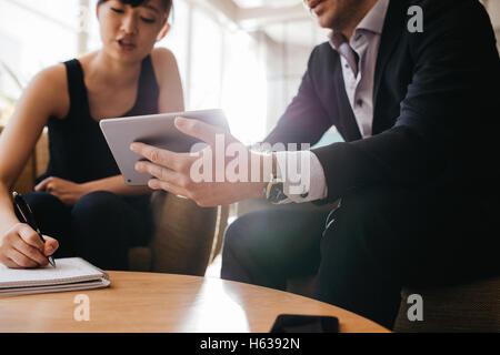 Bild der Geschäftsmann mit digital-Tablette und Frau mit Notepad beschnitten. Geschäftsleute sitzen in der Lobby - Stockfoto