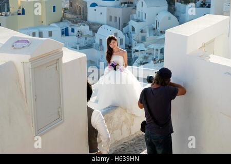 Eine chinesische Braut trägt eine Brautkleid ist im Dorf Oia auf der Insel Santorin in Griechenland fotografiert. - Stockfoto